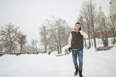Retrato exterior do inverno para o homem considerável novo com o telefone Adolescente bonito em seus revestimento e veste que lev foto de stock