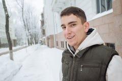 Retrato exterior do inverno para o homem considerável novo com o telefone Adolescente bonito em seus revestimento e veste que lev imagens de stock royalty free