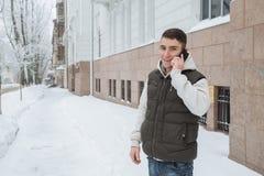 Retrato exterior do inverno para o homem considerável novo com o telefone Adolescente bonito em seus revestimento e veste que lev imagem de stock