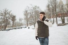Retrato exterior do inverno para o homem considerável novo com o telefone Adolescente bonito em seus revestimento e veste que lev foto de stock royalty free