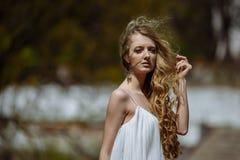 Retrato exterior do verão da menina consideravelmente bonito dos jovens Mulher bonita que levanta na ponte velha nos dess brancos foto de stock royalty free