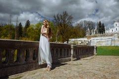 Retrato exterior do verão da menina consideravelmente bonito dos jovens Mulher bonita que levanta na ponte velha nos dess brancos fotos de stock royalty free
