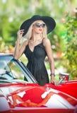Retrato exterior do verão da mulher loura à moda do vintage que levanta perto do carro retro vermelho fêmea justa atrativa elegan Imagem de Stock
