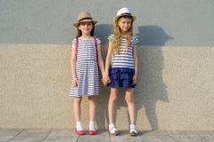 Retrato exterior do verão de duas namoradas felizes 7, 8 anos que guardam as mãos Meninas nos vestidos listrados, chapéus com tro imagens de stock royalty free