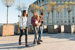 Retrato exterior dos estudantes adolescentes com trouxas que andam e que falam Fundo da cidade, hora dourada imagens de stock