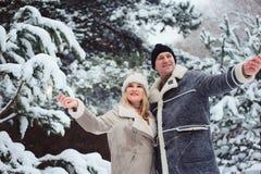 Retrato exterior dos pares românticos felizes que comemoram o Natal com os fogos-de-artifício ardentes na floresta nevado imagens de stock