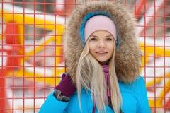 Retrato exterior nebuloso do inverno da mulher adorável feliz nova no revestimento ciano brilhante que levanta no parque da cidad imagens de stock royalty free