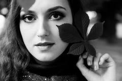 Retrato exterior preto e branco da mulher bonita com bordos sensuais e da composição profissional com a folha perto da cara Fotos de Stock Royalty Free
