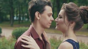 Retrato exterior sensível dos pares felizes bonitos que tocam levemente no parque video estoque