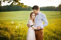 Retrato exterior sensual dos pares à moda novos que levantam no campo Fotografia de Stock Royalty Free
