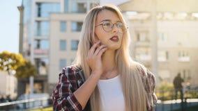 Retrato exterior uma jovem mulher loura que fala por seu smartphone imagem de stock