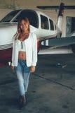 Retrato fêmea bonito no hangar do avião, com ai moderno Fotos de Stock Royalty Free