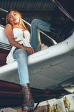 Retrato fêmea bonito no hangar do avião, com ai moderno Fotografia de Stock