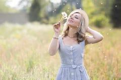 Retrato f?mea ao ar livre uma mulher em um chap?u de palha em um campo de flor com um ramalhete de flores selvagens fotografia de stock