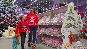 Retrato feliz da família da mãe que abraça com seu filho ao andar ao longo do shopping durante o Natal filme