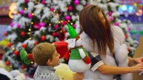 Retrato feliz da família na alameda durante feriados do Natal A mãe e o filho estão escolhendo os brinquedos de Santa Claus video estoque