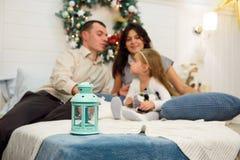 Retrato feliz da família no Natal, na mãe, no pai e na criança sentando-se na cama em casa, decoração dos chritmas em torno deles imagens de stock royalty free