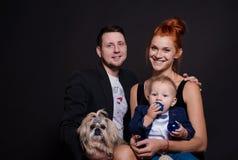 Retrato feliz de la familia con un niño pequeño y un perro en el estudio por el Año Nuevo fotos de archivo libres de regalías