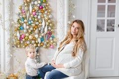 Retrato feliz de la familia en hogar - la madre embarazada de los jóvenes abraza a su pequeño hijo Feliz Año Nuevo Árbol de navid imágenes de archivo libres de regalías