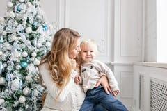 Retrato feliz de la familia en hogar - la madre embarazada de los jóvenes abraza a su pequeño hijo Feliz Año Nuevo Árbol de navid imagen de archivo