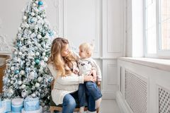 Retrato feliz de la familia en hogar - la madre embarazada de los jóvenes abraza a su pequeño hijo Feliz Año Nuevo Árbol de navid fotografía de archivo