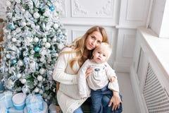 Retrato feliz de la familia en hogar - la madre embarazada de los jóvenes abraza a su pequeño hijo Feliz Año Nuevo Árbol de navid foto de archivo