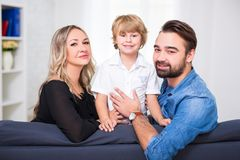Retrato feliz de la familia - pareja de los jóvenes y pequeña sentada linda del hijo Fotos de archivo libres de regalías