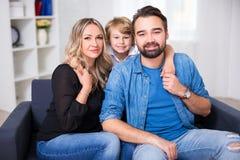 Retrato feliz de la familia - pareja de los jóvenes y pequeño hijo que se sientan en s Imagen de archivo libre de regalías