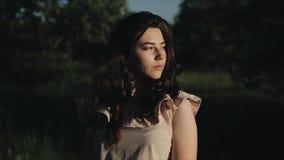 Retrato feliz de la forma de vida del primer de la chica joven caucásica bonita con el pelo negro rizado Sonrisas y miradas de la almacen de video