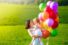 Retrato feliz de la madre y de la hija con los globos del color Imagen de archivo