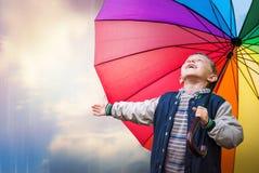 Retrato feliz del muchacho con el paraguas brillante del arco iris Imagen de archivo