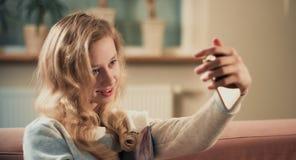 Retrato feliz del selfie de la toma de la muchacha del adolescente usando el teléfono móvil Foto de archivo