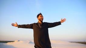 Retrato feliz do movimento lento do xeique masculino dos UAE do Arabian, que sorri e exulta na vida, estando entre o deserto larg filme