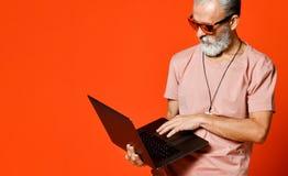 Retrato feliz do pensionista na moda que aprecia o uso do portátil novo imagens de stock