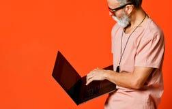 Retrato feliz do pensionista na moda que aprecia o uso do portátil novo fotos de stock royalty free