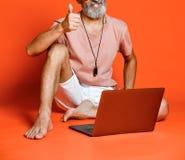 Retrato feliz do pensionista na moda que aprecia o uso do port?til novo fotos de stock royalty free