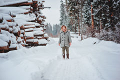 Retrato feliz engraçado da menina da criança na caminhada na floresta nevado do inverno com felling da árvore no fundo Imagens de Stock Royalty Free