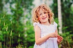 Retrato feliz lindo de la muchacha del niño en el paseo en bosque del verano Foto de archivo libre de regalías