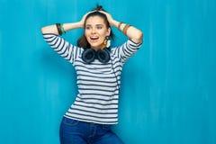 Retrato feliz sonriente de la muchacha del adolescente en fondo azul de la pared Imágenes de archivo libres de regalías