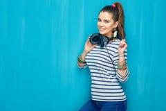 Retrato feliz sonriente de la muchacha del adolescente en fondo azul de la pared Foto de archivo