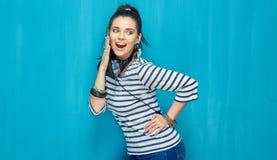 Retrato feliz sonriente de la muchacha del adolescente en fondo azul de la pared Foto de archivo libre de regalías