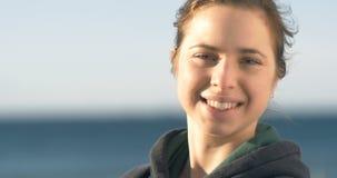Retrato femenino joven de mirada feliz sonriente del primer de la mujer almacen de video