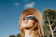 Retrato fresco de la chica joven con las gafas de sol y el sombrero al aire libre en naturaleza Imágenes de archivo libres de regalías
