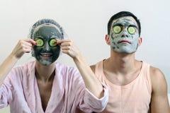 Retrato frontal de um casal com máscaras da argila em sua cara e pepinos na frente dele Termas em casa Cuidado de pele imagens de stock