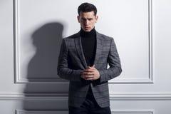 Retrato frontal de una presentación hermosa, elegante del hombre joven confiada en traje negro-gris elegante cerca de la pared bl fotos de archivo libres de regalías