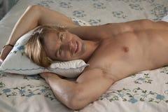 Retrato frontal del hombre que sonríe en cama Foto de archivo libre de regalías