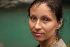 Retrato grande de una mujer contra un lago de la turquesa fotos de archivo