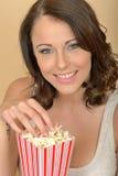 Retrato hermoso atractivo de la mujer joven que come las palomitas Foto de archivo libre de regalías
