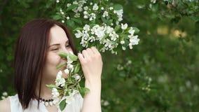 Retrato hermoso de la muchacha cerca de un árbol floreciente en el parque El concepto de juventud y de belleza natural Una chica  almacen de metraje de vídeo