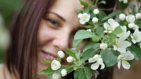 Retrato hermoso de la muchacha cerca de un árbol floreciente en el parque El concepto de juventud y de belleza natural Una chica  metrajes